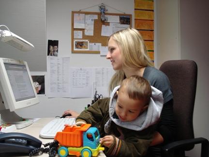 junge Dame mit dem Kind arbeitet am Computer